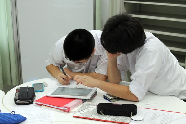 タブレットPCを使い企業を調べる生徒たち